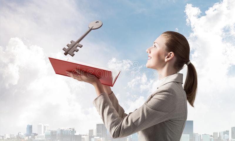 Woman looks at flying big metal key. Above open book. Real estate agency advertising. Sale of commercial or private real property concept. Elegant girl with royalty free stock photo