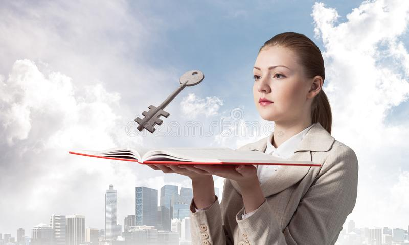 Woman looks at flying big metal key. Above open book. Real estate agency advertising. Sale of commercial or private real property concept. Elegant girl with royalty free stock photography