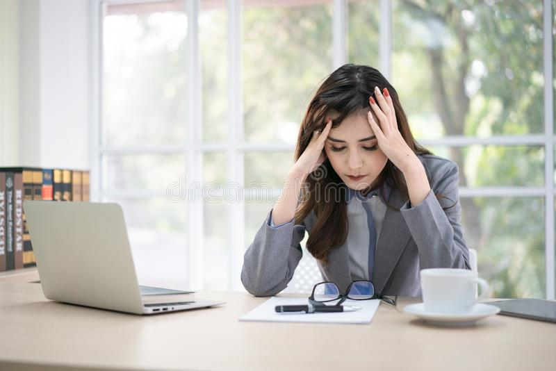 Woman looks at her laptop with a pained worried expression. Female employee is stressed out of work, touching aching head, reading royalty free stock photos