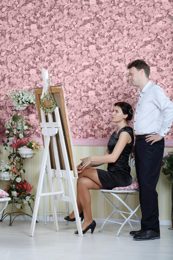 Woman looks at her portrait and talks with artist. In beautiful retro interior stock image