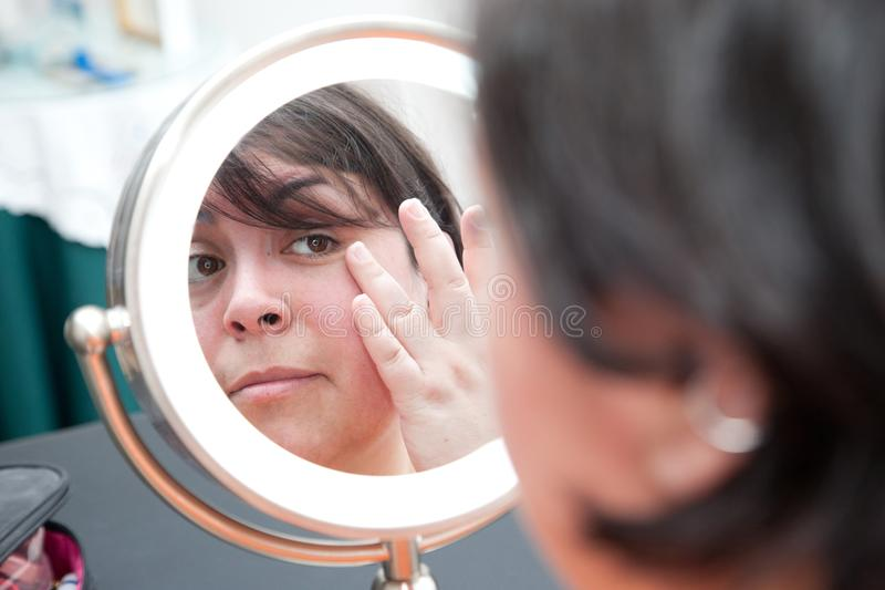 Checking face for blemishes. A woman looks at herself in a mirror and looks at her pores and skin, touching her eye stock photography