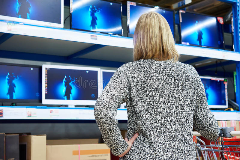 Woman looks at LCD TVs in shop. Woman looks at LCD TVs in supermarket stock photo
