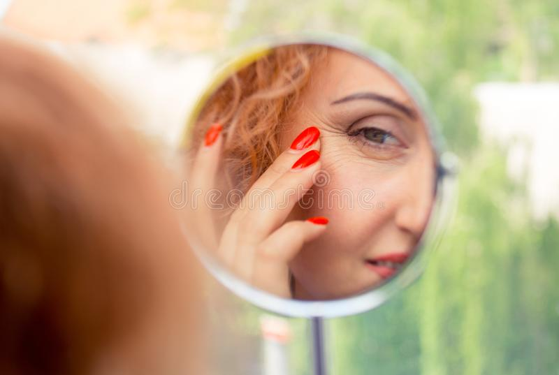 Woman looks in the mirror noticing the first wrinkles. Reflection in the mirror. A woman looks in the mirror noticing the first wrinkles, signs of aging. Anti stock photography
