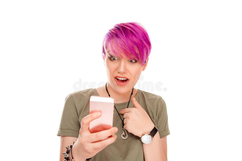Woman looks at modern smart phone with big eyes pointing to herself. Is it me? Really, You mean me? Pretty young female with pink hair looks at modern smart stock image