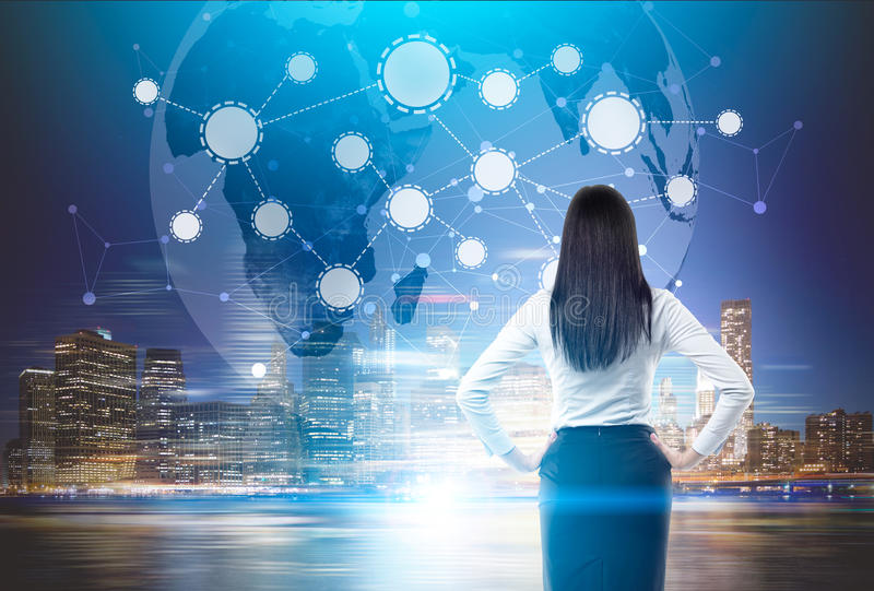 Woman looks at network sketch at night. Rear view of a woman with black hair standing with her arms on the waist and looking at network sketch at night. Elements stock photography