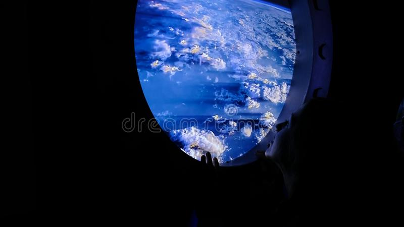 Woman looks out into the porthole in space stock photo