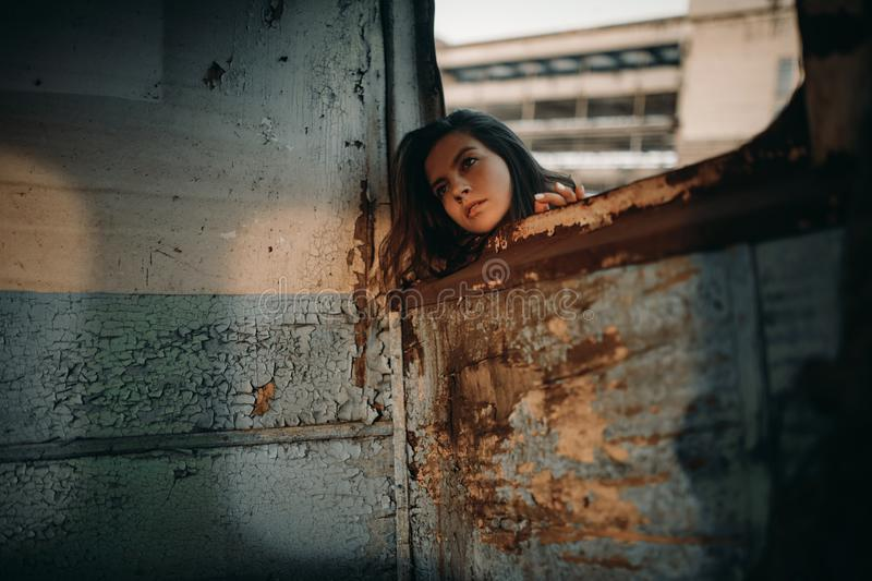 Woman looks out window of abandoned ship stock photos