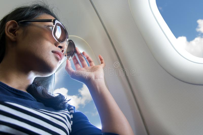 Woman looks out the window of an flying airplane. Woman with sunglasses looks out the window of an flying airplane. Young passengers are traveling by plane stock photos