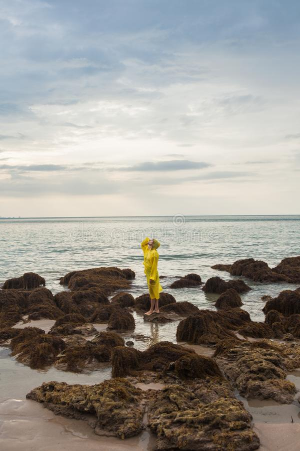 Woman in yellow raincoat standing In the ocean. Woman Looks Over The Ocean On A Windy Beach Wearing A Yellow Raincoat stock photos