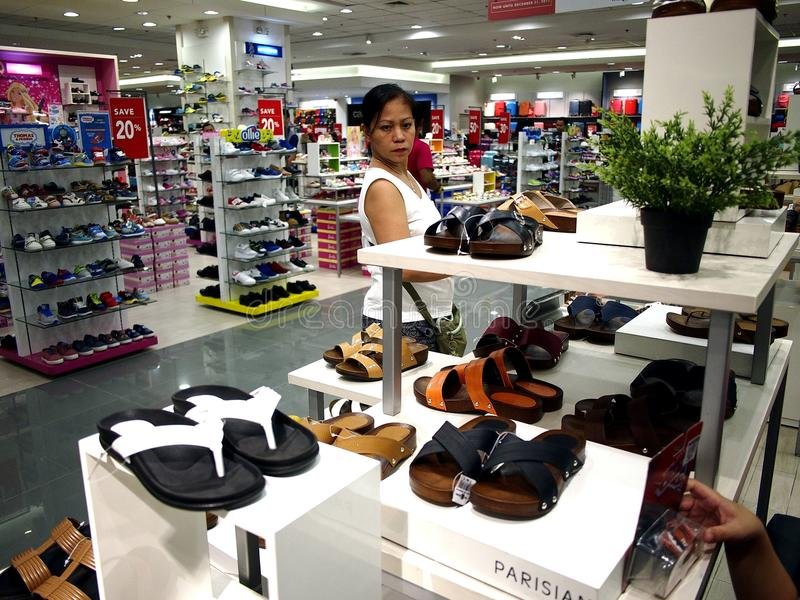 A woman looks at a pair of shoes in the shoe department of SM City mall in Taytay City, Philippines. TAYTAY CITY, PHILIPPINES - JULY 15, 2017: A woman looks at stock photography