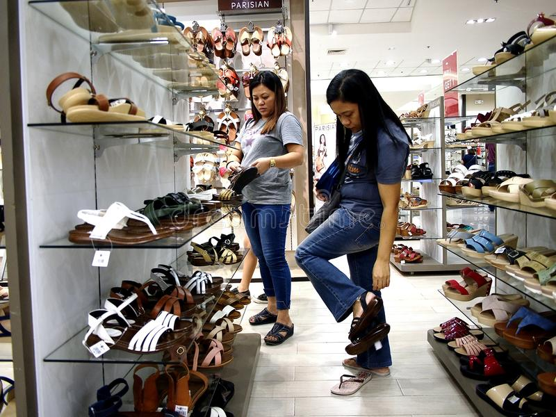 A woman looks at a pair of shoes in the shoe department of SM City mall in Taytay City, Philippines. TAYTAY CITY, PHILIPPINES - JULY 15, 2017: A woman looks at stock photos