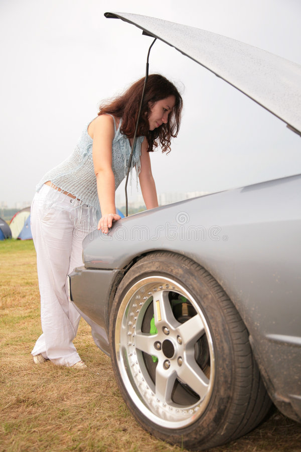 Free Woman Looks Under A Car Cowl Royalty Free Stock Image - 8147556
