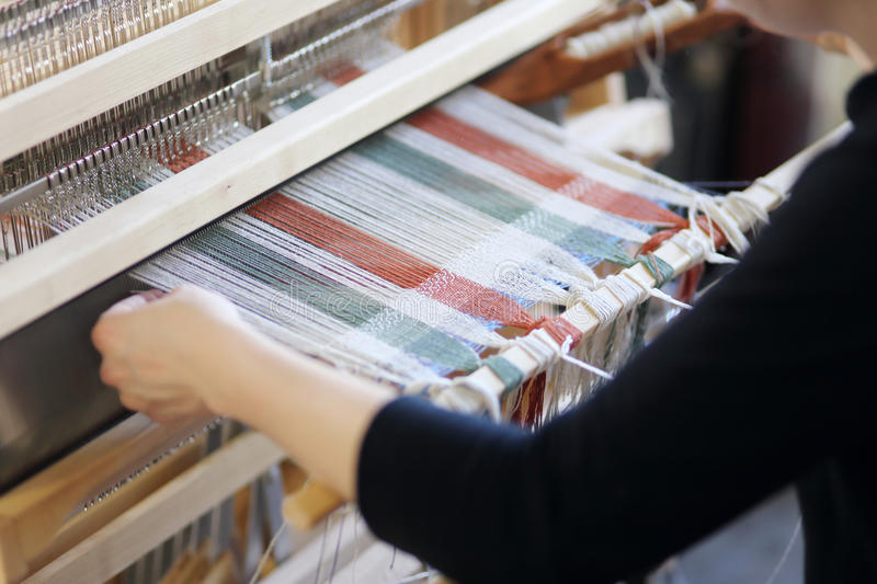 Woman with loom. Woman using a foot-treadle floor loom with threads royalty free stock images