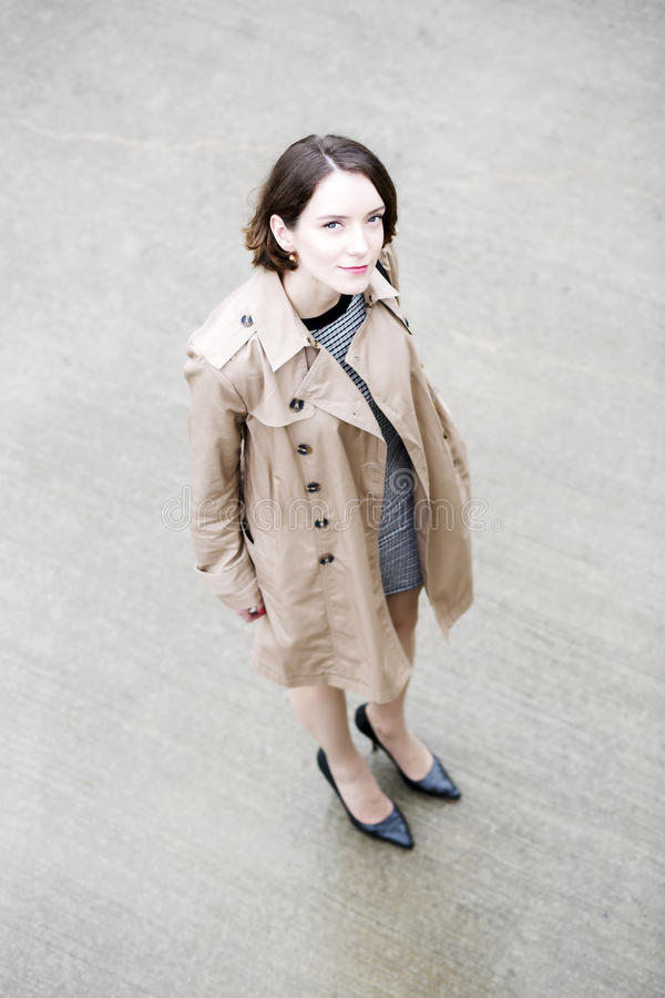 Woman at loose beige coat on greyish square stock photo