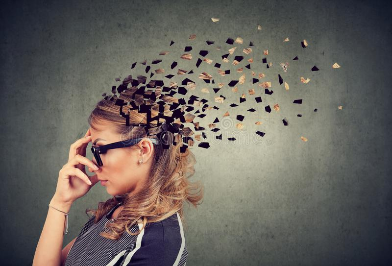 Woman losing parts of head as symbol of decreased mind function. Memory loss due to dementia or brain damage. Side profile of a woman losing parts of head as stock image