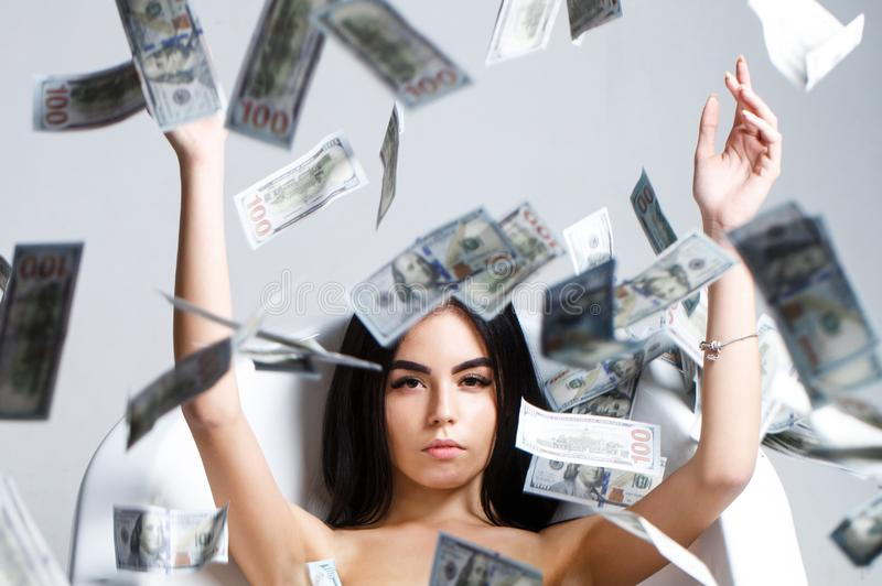 Woman with lot of money. Millionaire woman lying in bedroom. Sexy woman lying in dollar bills. Rich sexy woman lies on stock photos