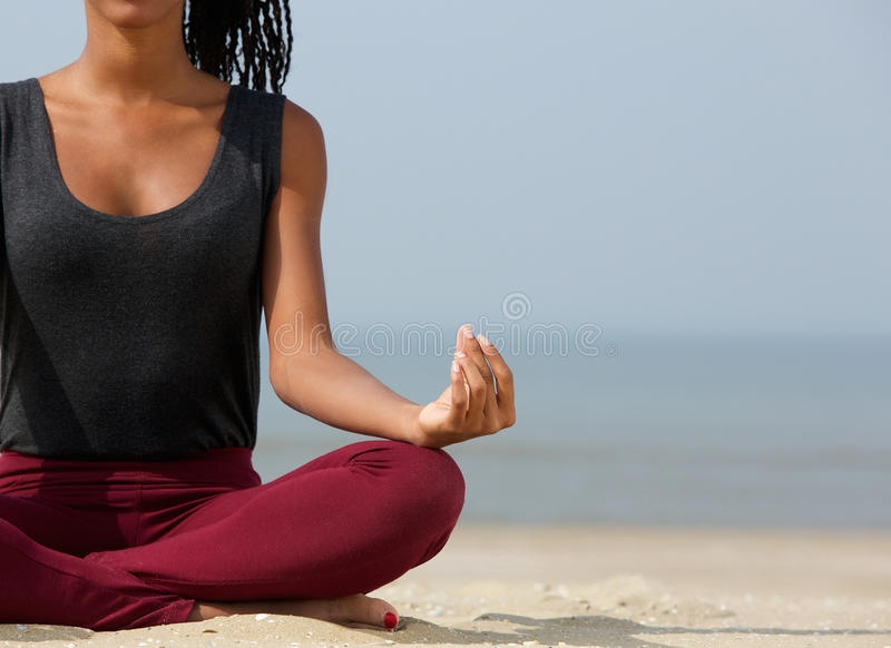 Woman in lotus position. Close up portrait of a young woman in lotus position with yoga hands at the beach stock photography