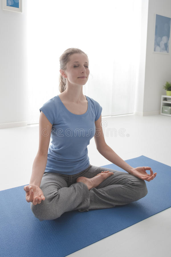 Woman in lotus position. Young woman practicing yoga and meditation at home on the floor, she is sitting in the lotus position and relaxing royalty free stock photography