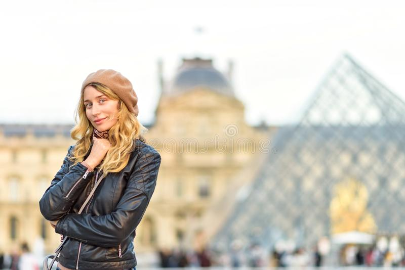 Woman at Louvre in Paris, France. Young tourist girl admiring the views. French style. Portrait soft bokeh backgrounds royalty free stock image