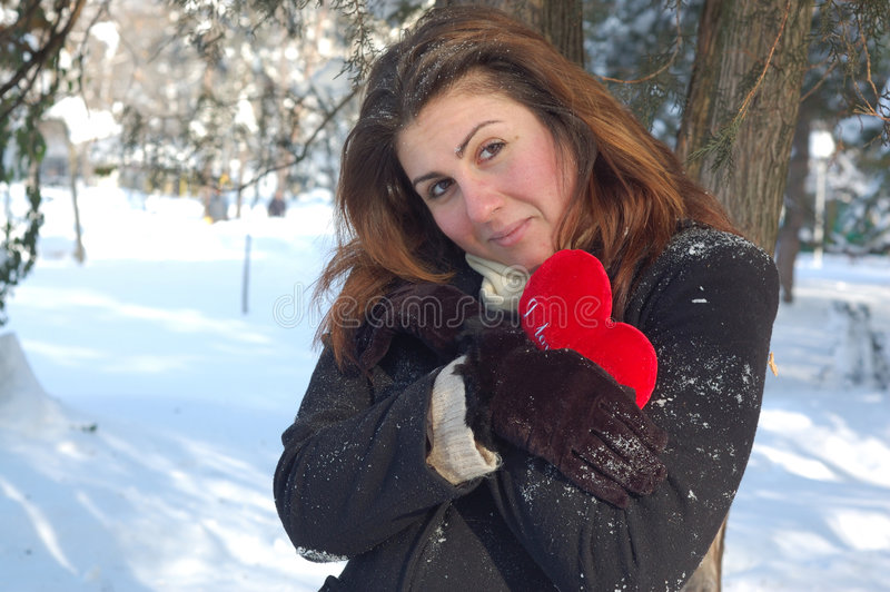 Woman with love heart in snow stock image