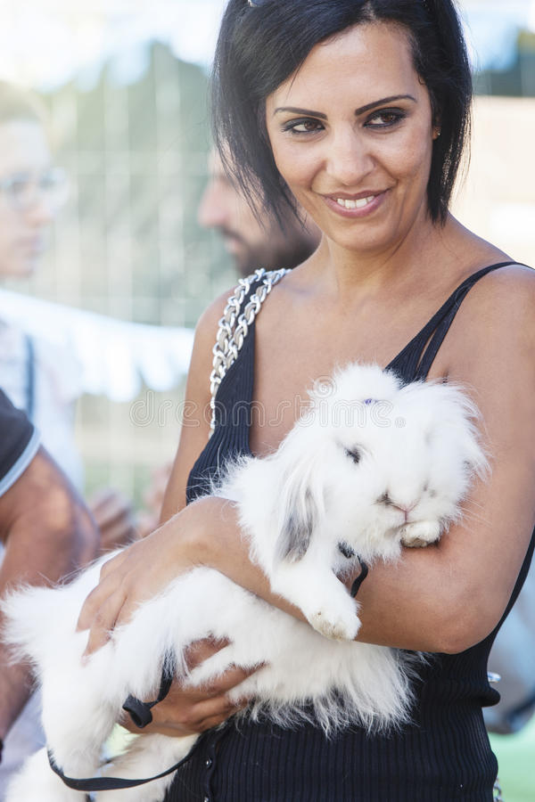Woman loving her rabbit. Embracing in her arms royalty free stock images