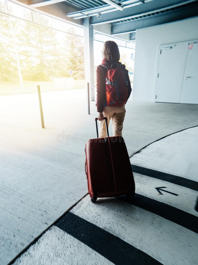 Woman with luggage exit airport parking to terminal royalty free stock photo