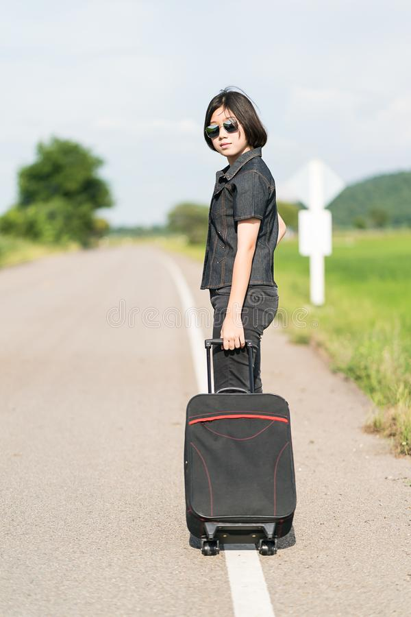 Woman with luggage hitchhiking along a road. Young asian woman short hair and wearing sunglasses with luggage hitchhiking along a road in countryside Thailand royalty free stock image
