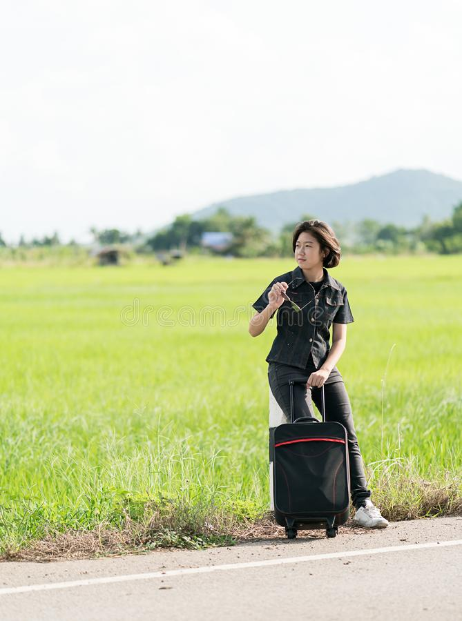 Woman with luggage hitchhiking along a road. Young asian woman short hair and wearing sunglasses with luggage hitchhiking along a road in countryside Thailand stock images