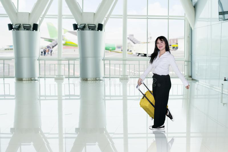 Woman with luggage smiling in airport terminal royalty free stock photo