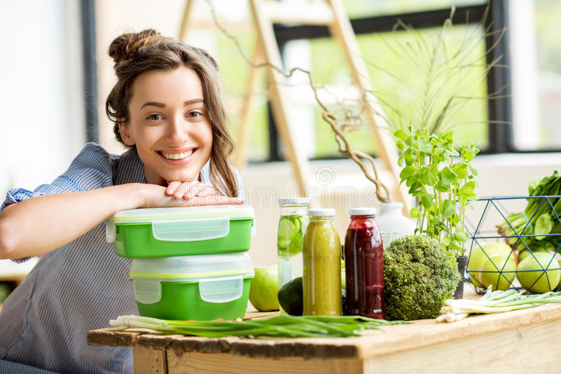Woman with lunch boxes. Portrait of a young smiling woman with green lunch boxes indoors stock images