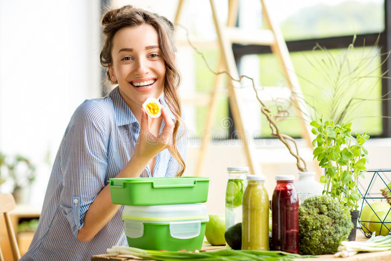 Woman with lunch boxes. Young woman prapairing food in green lunch boxes sitting on the table indoors royalty free stock photos