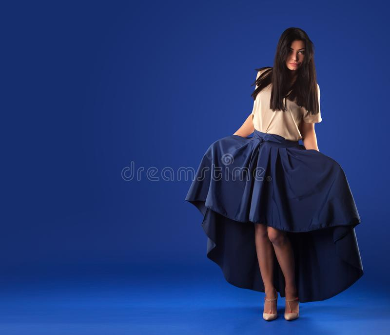 Woman in a lush long skirt posing on a blue studio background. Beautiful brunette woman in a lush long skirt posing on a blue studio background stock photo