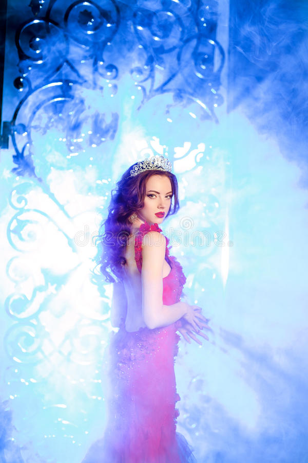 Woman in lux dress with crown like queen, princess, lights party. Background Luxury girl Long shiny healthy volume hair. Waves Curls Updo Hairstyle. Salon stock image