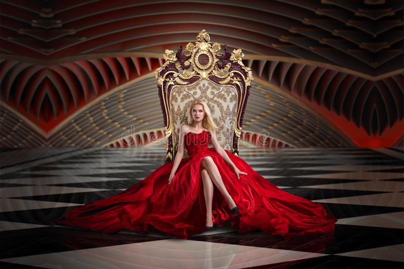 Blonde woman sitting on the throne. A woman in a luxurious gown dress sitting on a queen`s throne stock photography