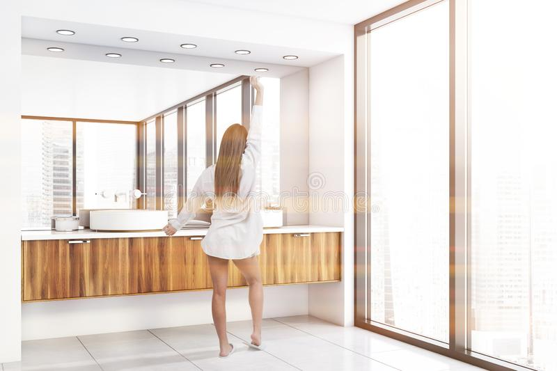 Woman in luxury bathroom with double sink. Young woman in nightgown standing in modern bathroom interior with panoramic window, white walls and double sink royalty free stock image