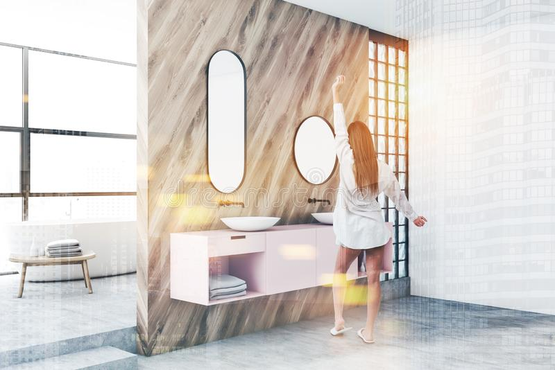 Woman in luxury bathroom with pink double sink royalty free stock image