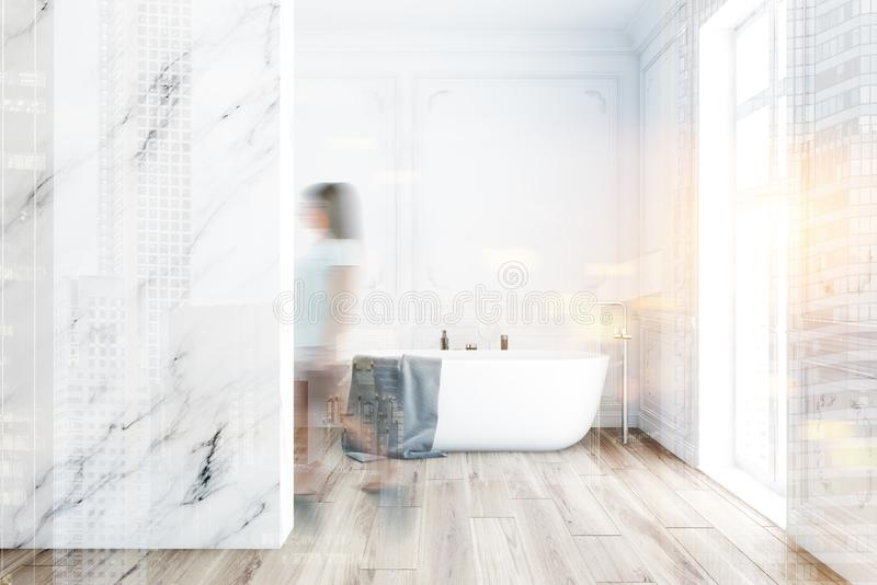 Woman in luxury marble bathroom with tub. Blurry young woman walking in luxury bathroom interior with white and marble walls, wooden floor and comfortable royalty free stock image