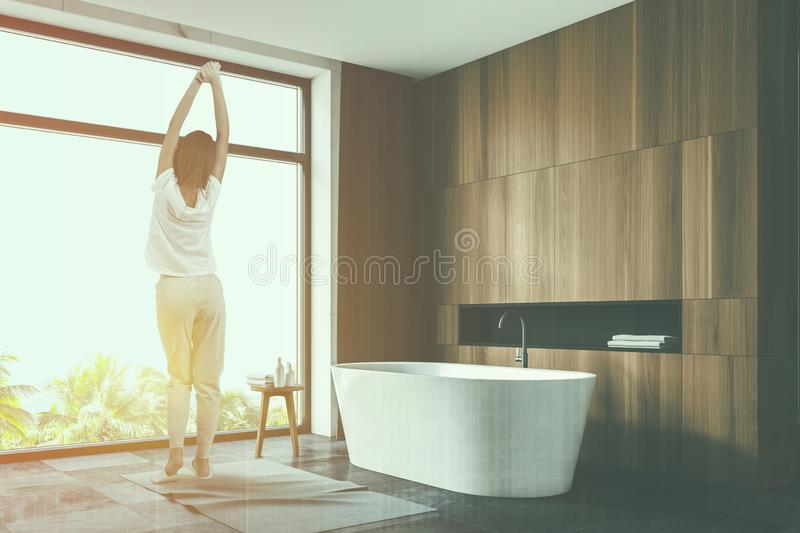 Woman in luxury wooden bathroom interior. Rear view of woman in pajamas standing in stylish bathroom with wooden walls, tiled floor, panoramic window with royalty free stock image