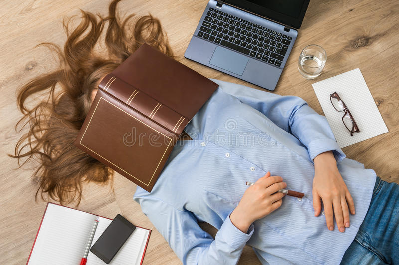 Woman lying on back and covering her face with book royalty free stock image