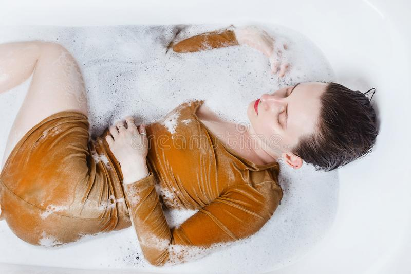 Woman lying in bathtub filled with charcoal bath bomb, selective focus stock image