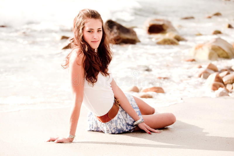 Woman lying in the beach sand. Young woman lying in the sand at the beach royalty free stock photography