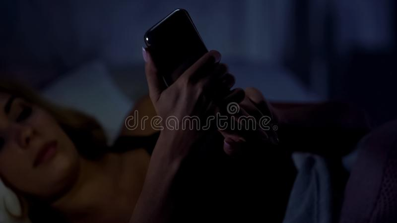 Woman lying in bed and chatting on smartphone, online shopping, gadget addiction. Stock photo stock image