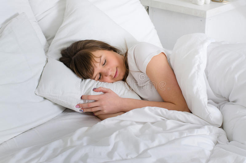 Woman lying in bed comfortably stock photo