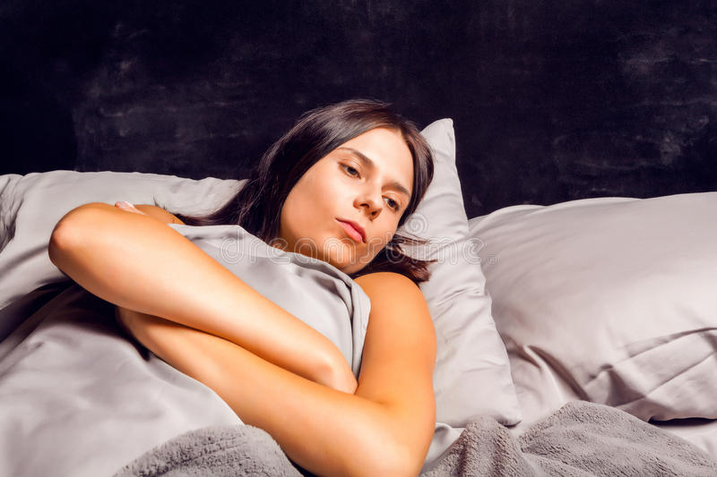 Woman lying in bed on a dark background with open eyes. Beautiful young brunette in bad mood lying in bed royalty free stock photography