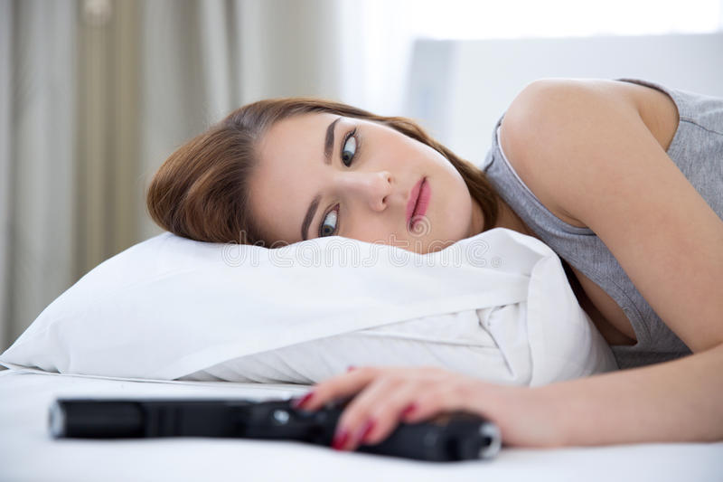 Woman lying on the bed with gun stock images