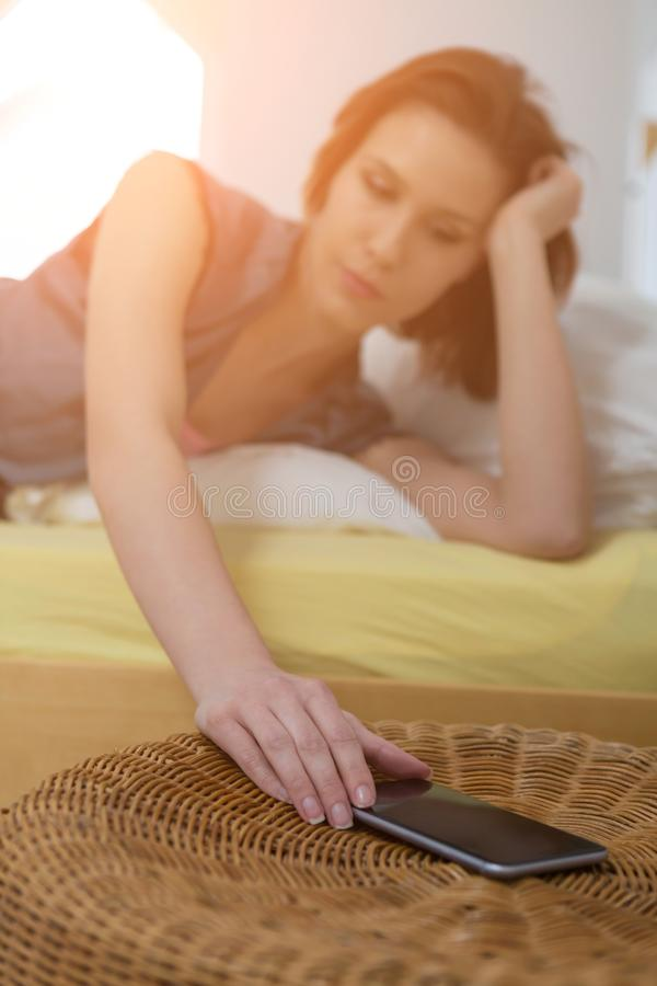 Woman lying on a bed reaching for a mobile phone. Backlit by bright flare from a lamp royalty free stock photography