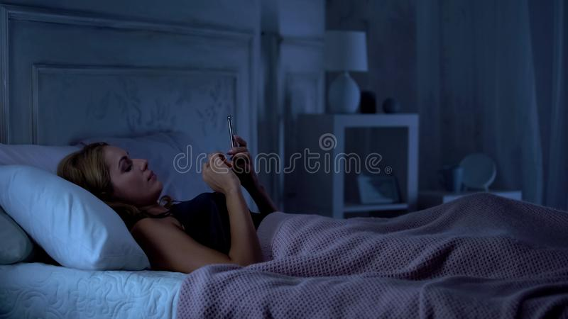 Woman lying in bed and reading news on smartphone at night before sleeping stock image