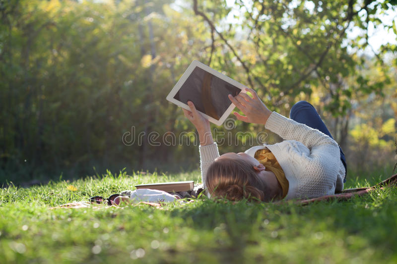 Woman lying on bedding on green grass with ipad stock photography