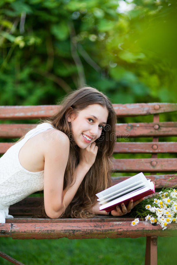 Download Woman Lying On Bench With Book Stock Photo - Image: 25747898