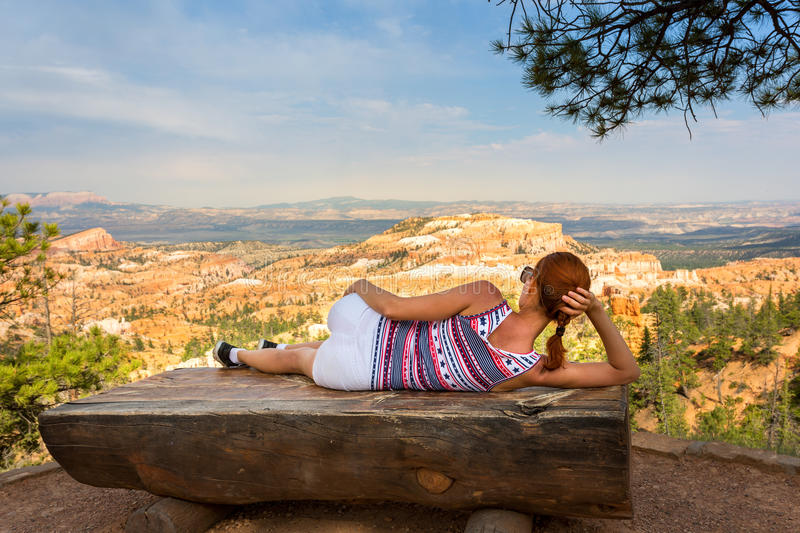 Woman lying on bench at the top of rocky mountain stock photography